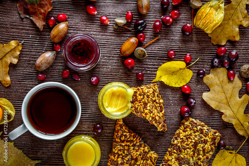 Fotografering  Hot tea with honey and berries on wooden background