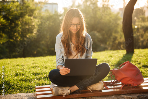 Happy brunette woman in eyeglasses sitting on bench Fototapet