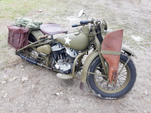 Military Motorcycle With A Leather Rifle Holster Attached To A Front Wheel. The Vehicle Is Painted Khaki Or War Color.