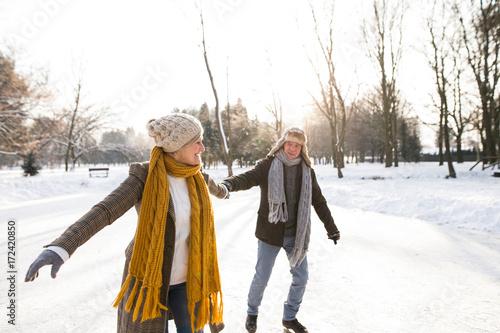 Obraz Senior couple in sunny winter nature ice skating. - fototapety do salonu