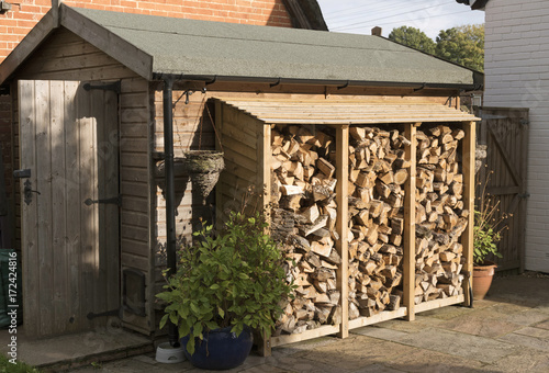 Obraz na płótnie Log store standing against a garden shed