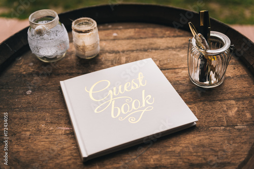 Guest book on wooden barrel surrounded by glasses Canvas Print