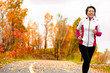 canvas print picture - Mature happy middle age woman jogging outside in her 50s. Middle aged Asian chinese girl in her fifties jogging outdoor living healthy lifestyle in beautiful autumn city park in colorful fall foliage.
