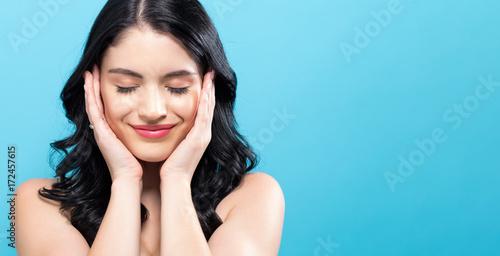 Fotografie, Tablou  Beautiful young woman touching her face in skin care theme