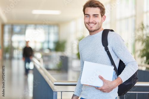 Foto  Junger Student mit Unterlagen freut sich
