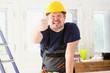 Smiling funny worker in yellow helmet posing