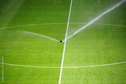 Obraz Bewässerung Fußballrasen / Die grüne Rasenfläche eines Fußballfeldes mit einer Bewässerungsanlage. - fototapety do salonu