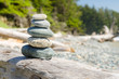 Stack of Balanced Stones on Driftwood on a Beach on a Sunny Spring Day. Concept of Meditation and Harmony.