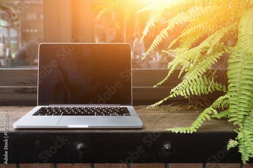 Keuken foto achterwand Peking Laptop with blank screen on table, Coffee shop blurred background