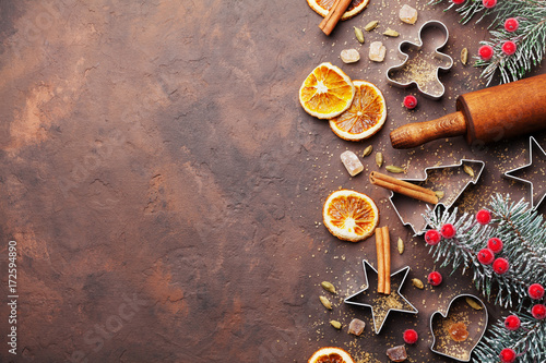 Holiday christmas background for baking cookies with cutters, rolling pin and spices on brown table top view. Copy space for text.