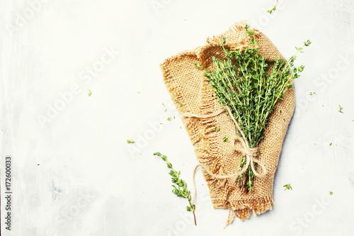 Fototapeta Fresh thyme on canvas napkin, gray background,  top view