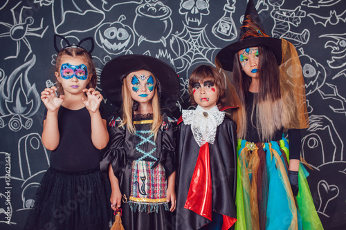 Staande foto Kinderkamer Children in scary Halloween costumes stand against a wall with drawings.