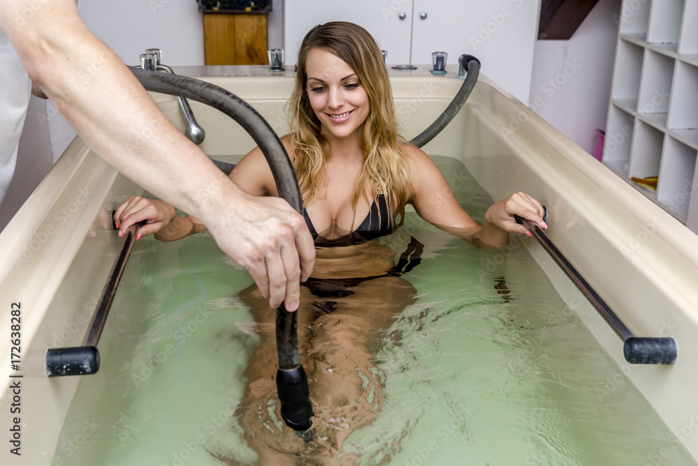 Fototapeta Woman enjoying the hydrotherapy massage. Targentor is the name of the hydrotherapic water massage.