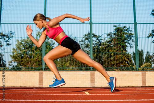 Runner sprinting towards success on run path running athletic track Fototapeta