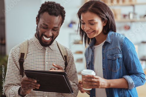 Upbeat friends checking cafe menu on tablet Canvas Print