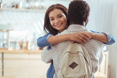 Happy woman hugging her best friend in cafe Canvas Print