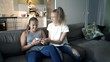 Sisters fighting over smartphone on sofa at home