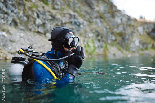 Male diver in wetsuit checking equipments before immerse