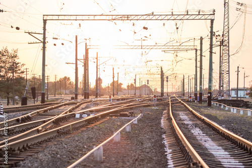 Montage in der Fensternische Eisenbahnschienen An empty railway sorting station or terminal with lots of junction, crossroads, semaphore showing red or green light, in a bright sunset light.