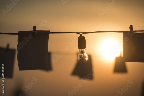 Foto op Canvas Licht, schaduw Light bulbs and papers at sunset
