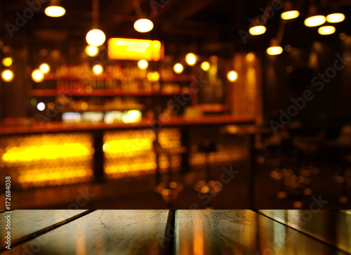 top of wood table with light reflection with abstract blur bar or club in the dark night background