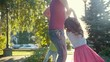 Father playing with children - little boy and girl in summer park at sunset - slow-motion