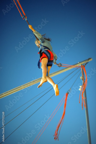 Valokuvatapetti Little girl on bungee trampoline with cords