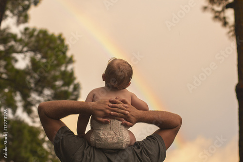 Rear view of father carrying son on shoulders , looking at rainbow