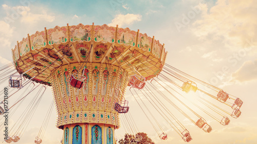 Foto  carousel ride spins fast in the air at sunset - vintage filter effects - a swing