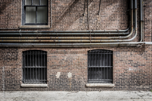 Three windows on a bricks with pipes