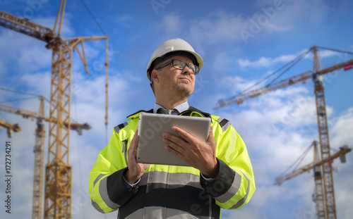 Construction engineer wearing safety vest with yellow crane on the background