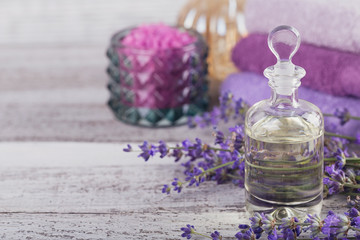 Obraz na płótnie Canvas Bottle of essential oil and fresh lavender flowers on a white wooden background. Aromatherapy, spa and wellness concept