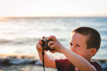 Young Boy Taking Digital Photo...