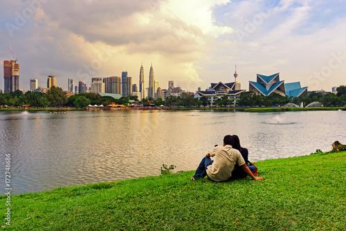 Fotografia, Obraz  Unidentified couple at Taman Tasik Titiwangsa during sunset with Kuala Lumpur skyline, Kuala Lumpur, Malaysia
