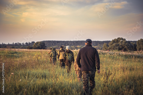 Group of people in a row going away through rural field at sunset during hunting season in countryside
