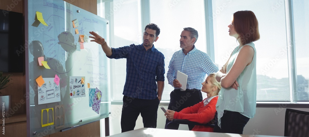Fototapeta Young businessman discussing with colleagues at office