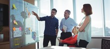 Young Businessman Discussing With Colleagues At Office