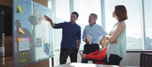 Cuadros en Lienzo Young businessman discussing with colleagues at office
