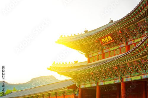 """Zdjęcie XXL Słońce za dachem bramy do Pałacu Gyeongbokgung - tłumaczenie na to słowo to """"Gyeongbokgung Palace"""" - Seul, Korea Południowa"""