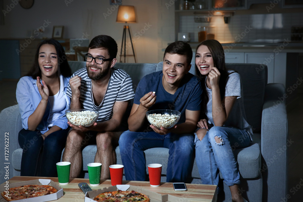 Fototapety, obrazy: Friends watching TV in evening at home
