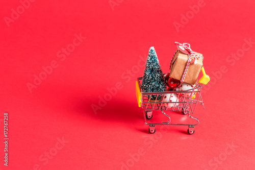 Fotografering  Holiday shopping theme with shopping cart filled with giftboxes