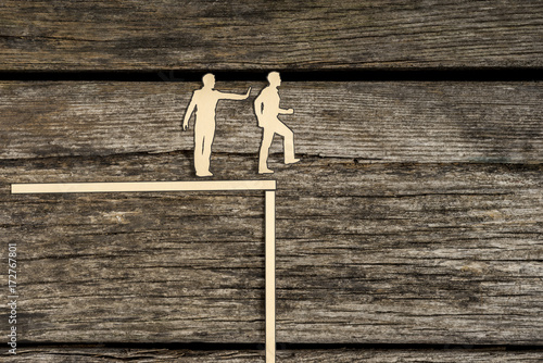 Fotografia Silhouette cutout men standing next to each other as one pushes another off the
