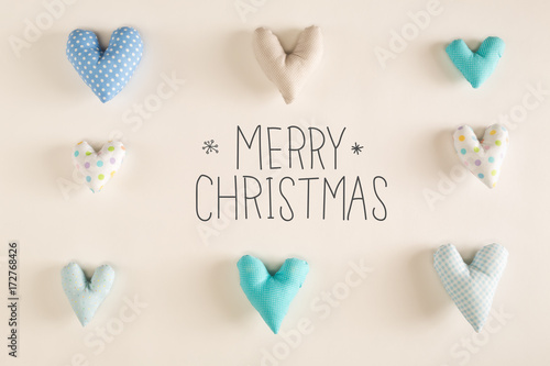 Merry Christmas message with blue heart cushions on a white paper ...