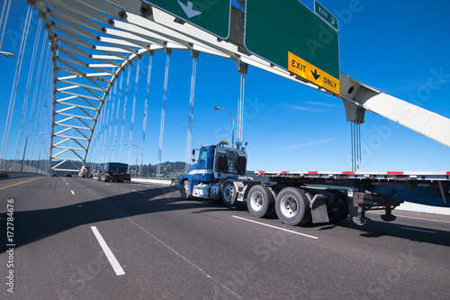 Tuinposter Industrial geb. Blue big rig semi truck with day cab and flat bed semi trailer driving on the arched bridge