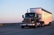 Leinwanddruck Bild - Dark big rig semi truck with bulk trailer running on highway in sunset light