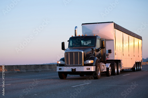 Платно Dark big rig semi truck with bulk trailer running on highway in sunset light