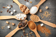 Various Kinds Of Sugar In Wooden Spoons On Grey Table