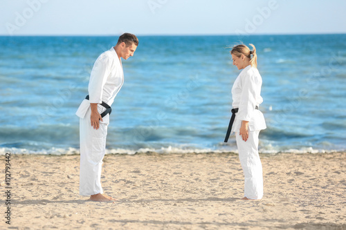Garden Poster Martial arts Young man and woman performing ritual bow prior to practicing karate outdoors