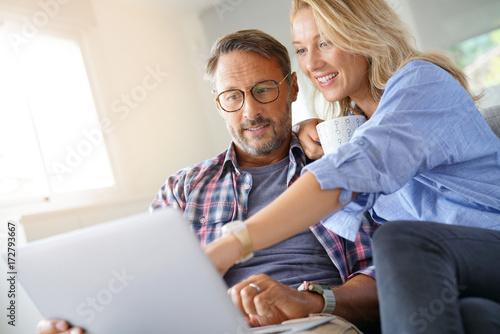 Fototapeta Mature couple connected on internet with laptop obraz