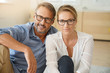 canvas print picture Mature couple with eyeglasses sitting on carpet at home